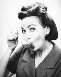 A woman tasting from a spoon.