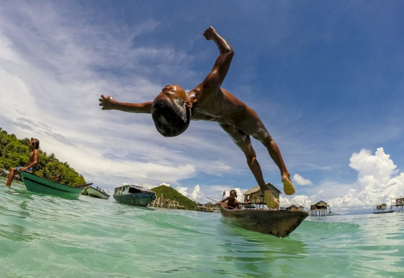 Boy jumping into clear sea water, Malaysia