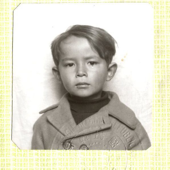 A passport photo of Thomas as a boy just before coming to the United States for his adoption,